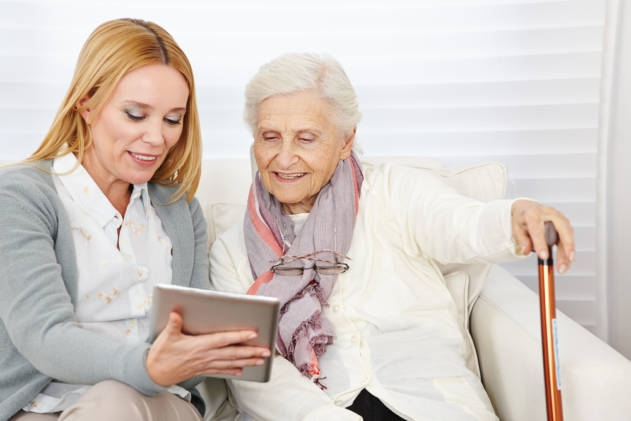 nurse helping senior with online shopping